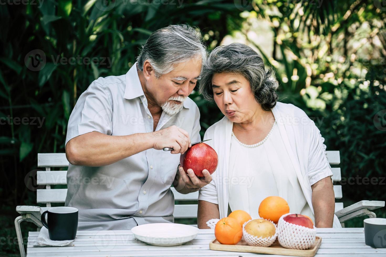 coppia di anziani affettare e mangiare frutta foto