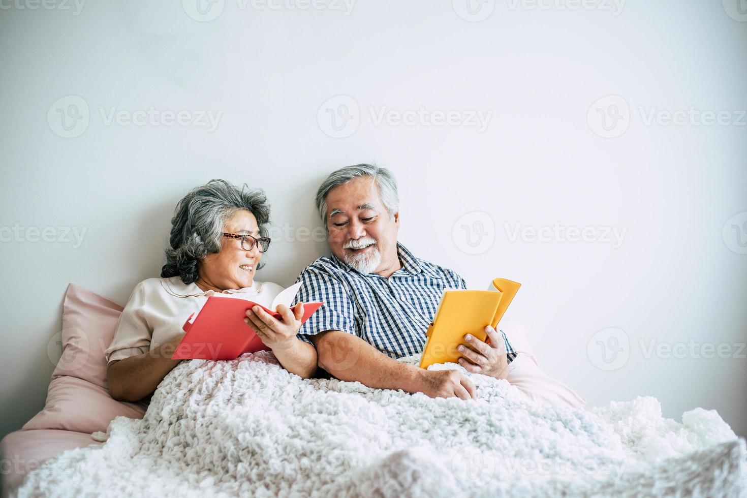 coppia di anziani sdraiata sul letto e leggere un libro foto