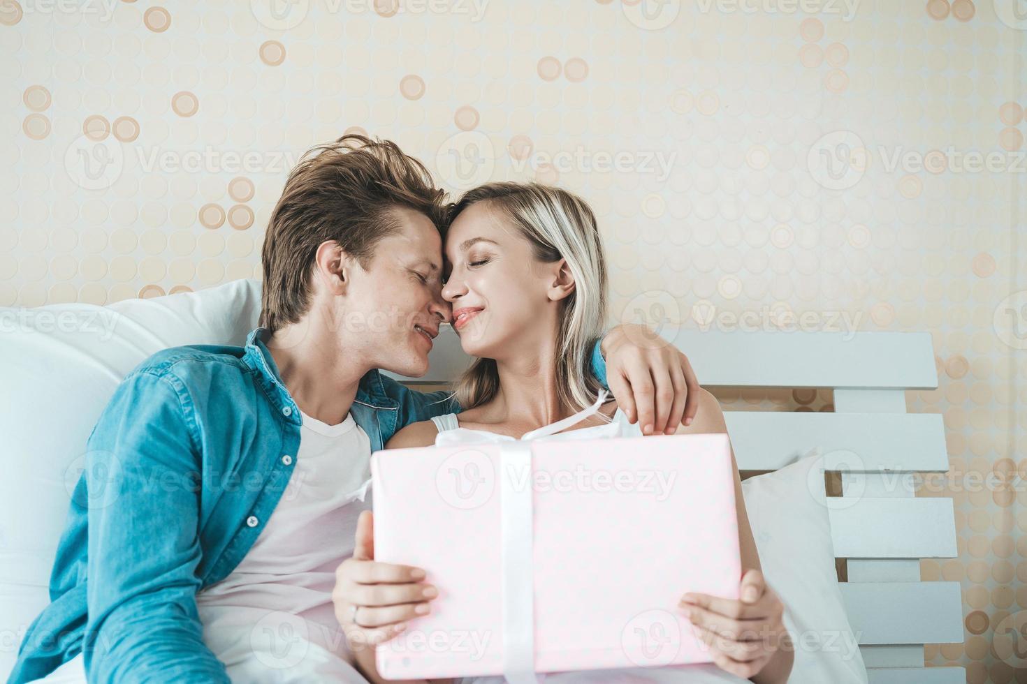 il ragazzo sorprende la sua ragazza con una confezione regalo sul letto foto
