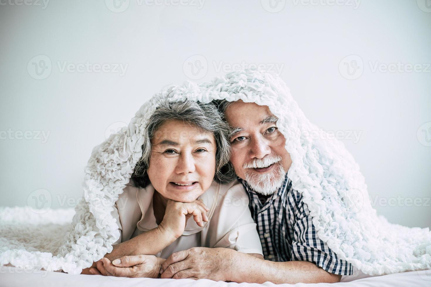 felice coppia senior ridendo in camera da letto foto