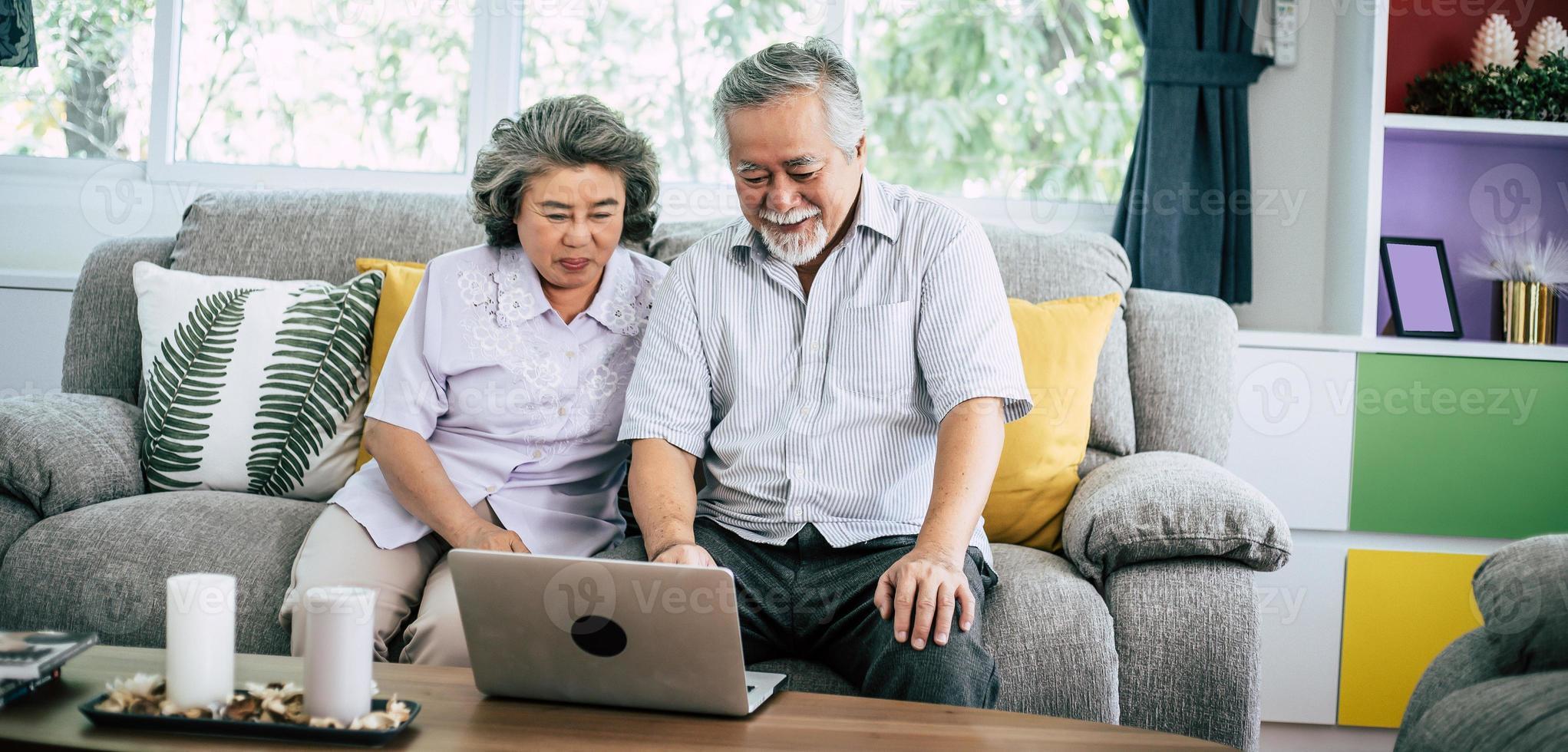 coppia senior parlando e utilizzando il computer portatile foto