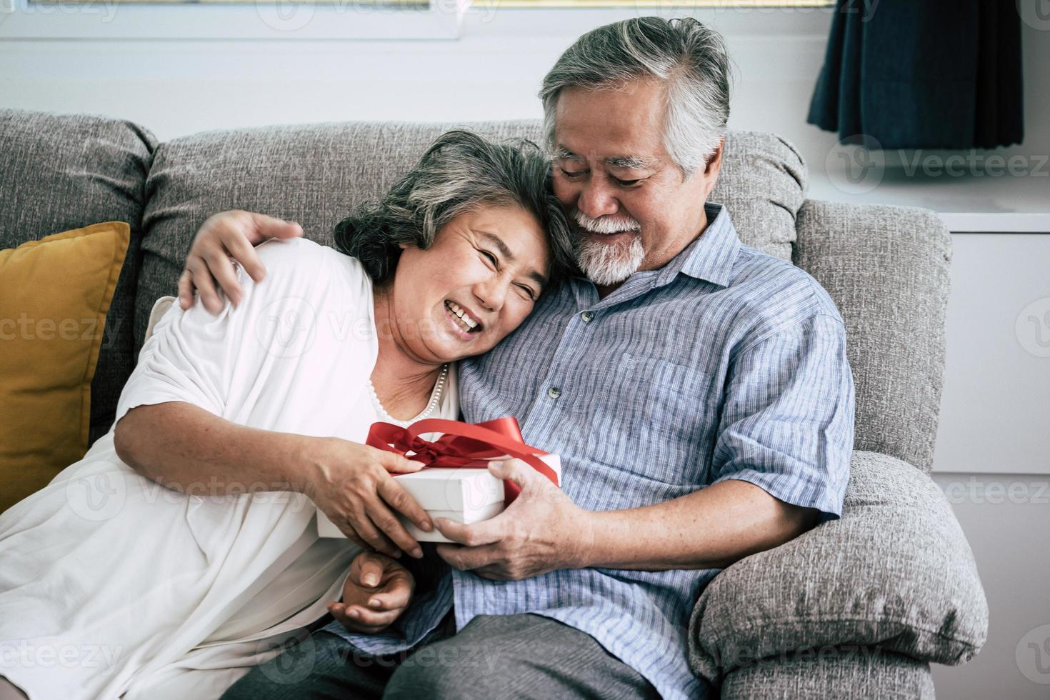 sorprese coppia di anziani con confezione regalo in soggiorno foto