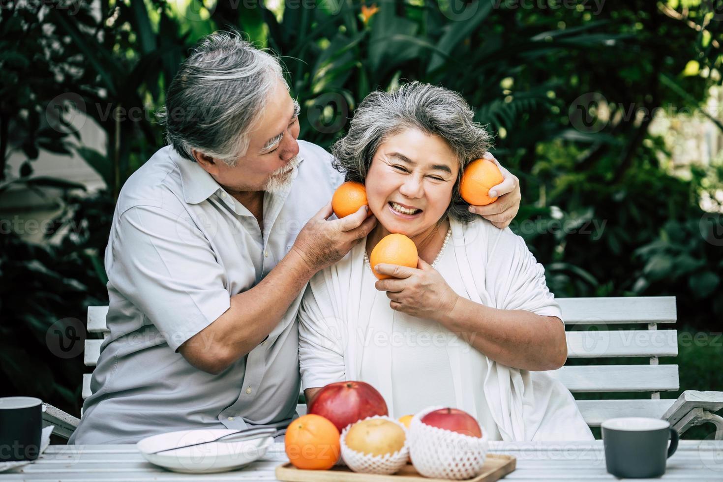 coppia di anziani giocando e mangiando un po 'di frutta foto