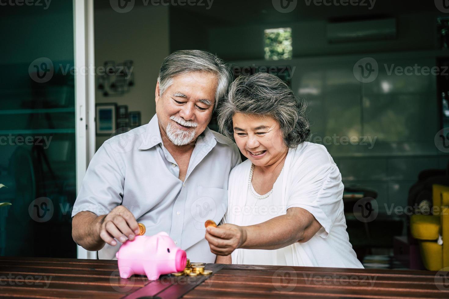 coppia di anziani parlando di finanze con salvadanaio foto