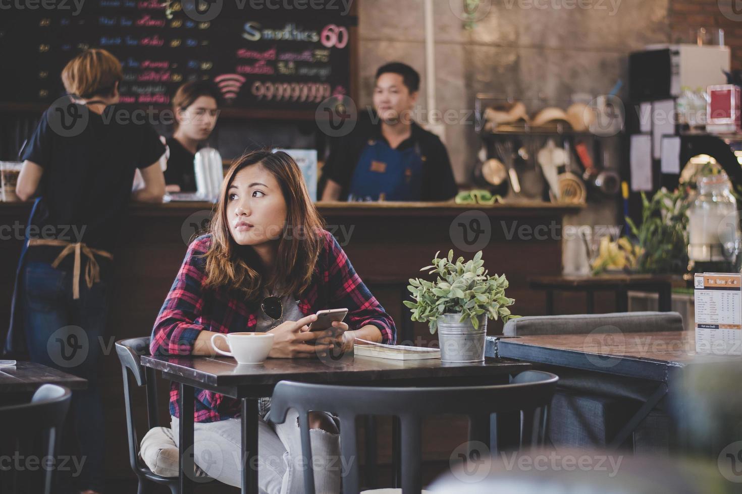 Ritratto di donna giovane hipster utilizzare il telefono cellulare mentre è seduto nella caffetteria tabella foto