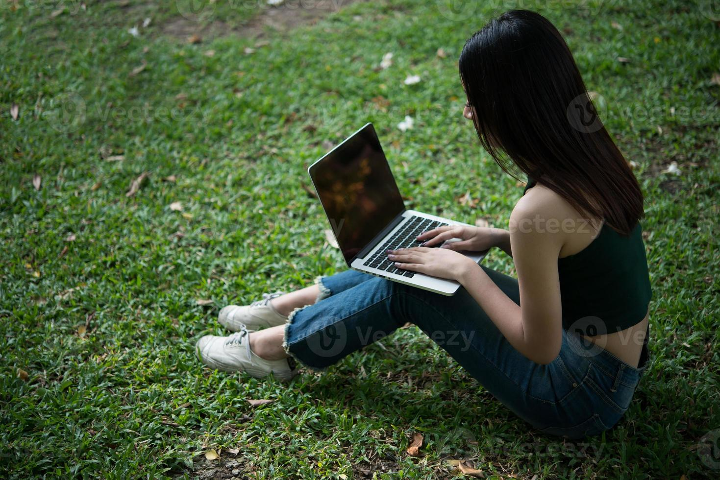 giovane bella donna seduta sull'erba verde e utilizzando il computer portatile nel parco foto