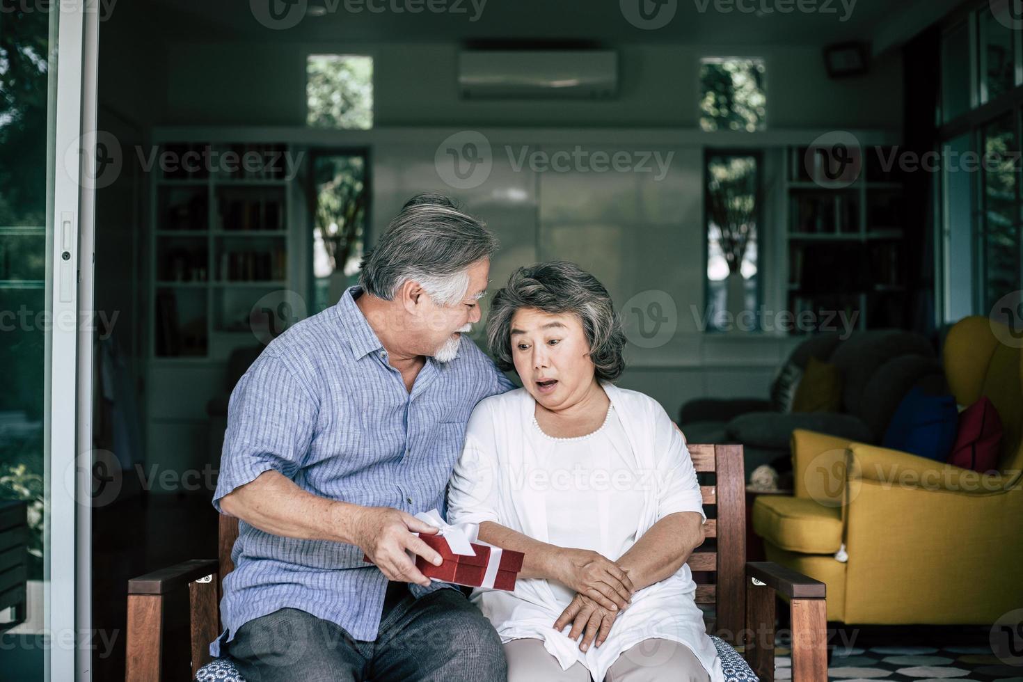 sorridente senior marito facendo sorpresa dando confezione regalo a sua moglie foto
