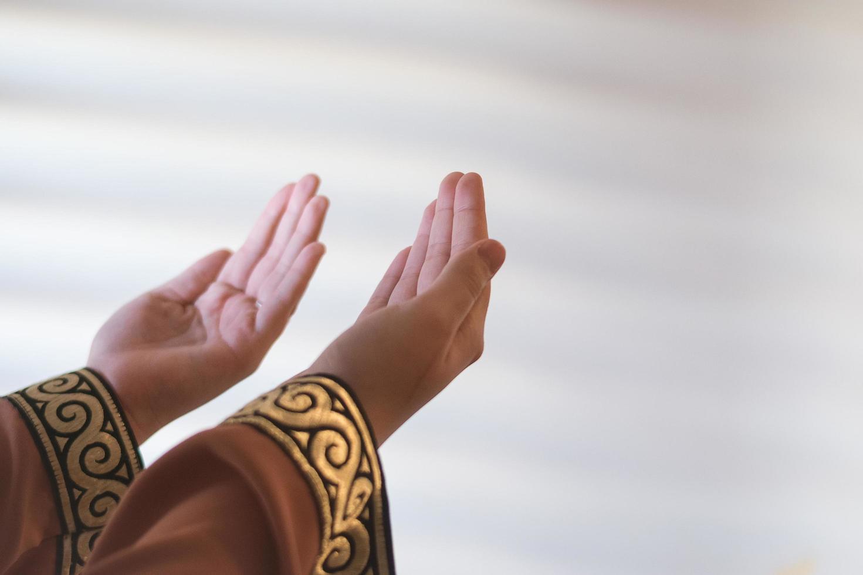 mani di una donna musulmana o islamica gesticolando mentre pregava a casa foto