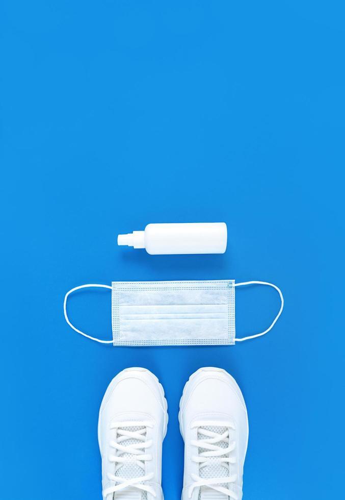 maschera medica bianca, scarpe da ginnastica e disinfettante per le mani su sfondo blu, piatto verticale monocromatico foto
