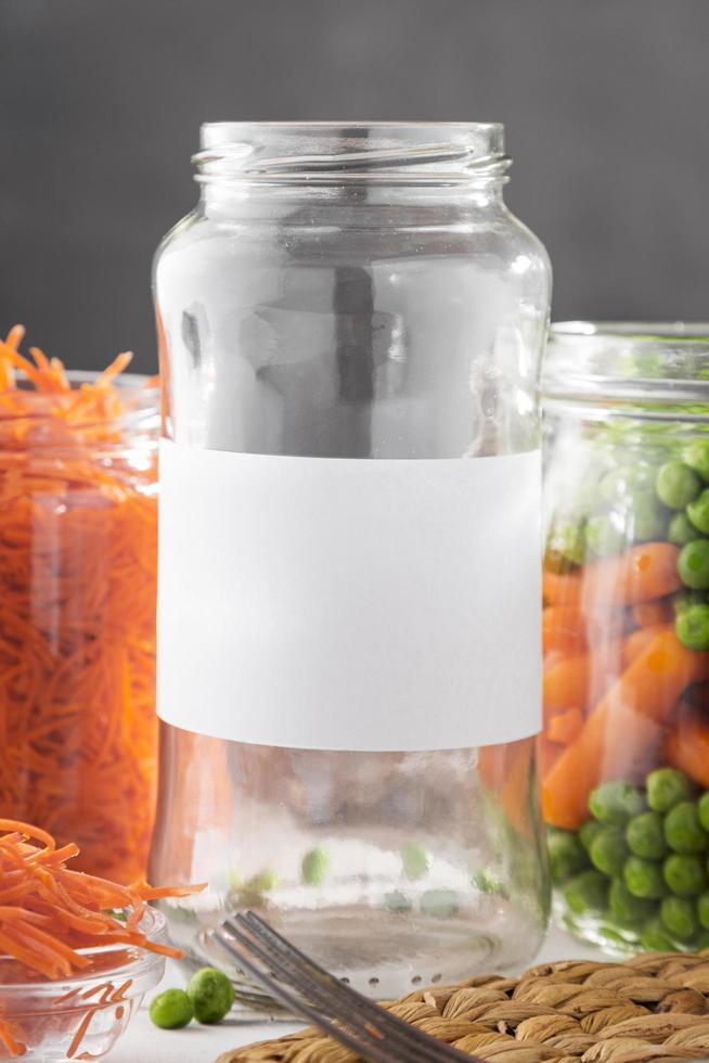 vista frontale di piselli sottaceto e carotine in vasetti di vetro trasparente foto