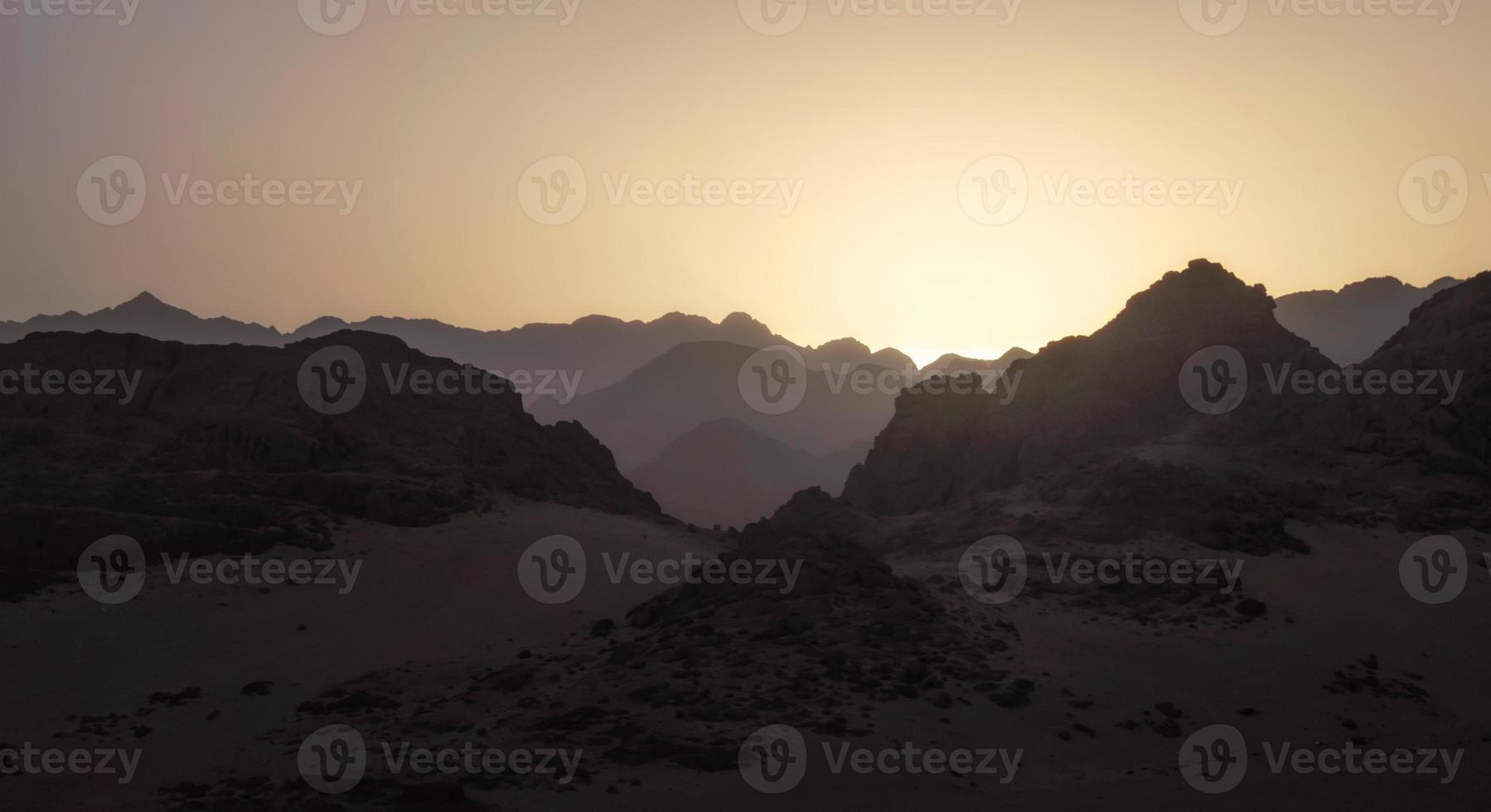 montagne rocciose con un sole al tramonto foto