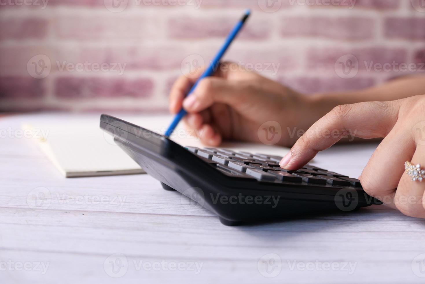 mano utilizzando la calcolatrice sulla scrivania in ufficio foto
