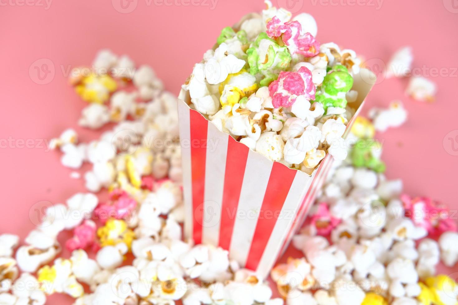 popcorn fuoriuscita da un contenitore su sfondo rosso foto