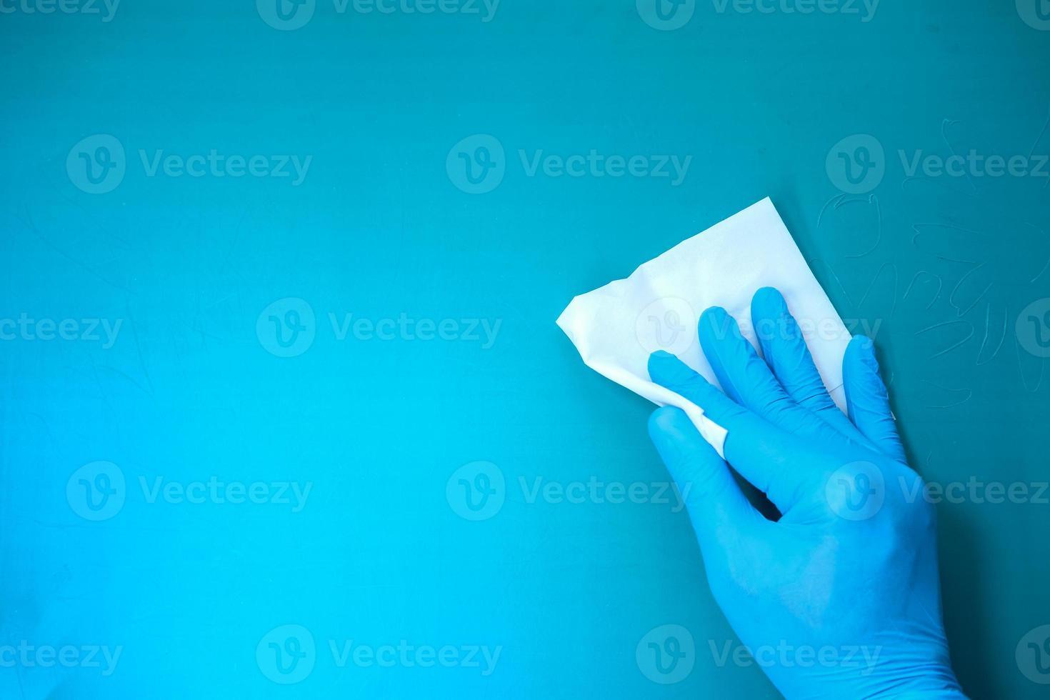 mano in guanti di gomma blu che puliscono il tavolo con un panno foto