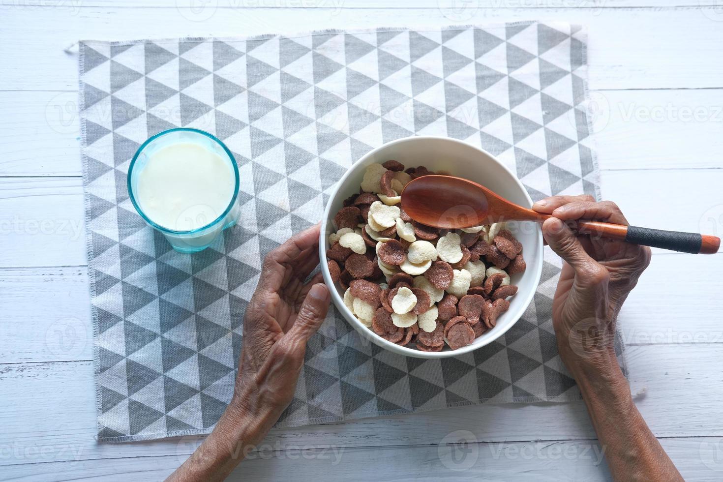 vista dall'alto delle donne anziane che mangiano i fiocchi di mais al cioccolato in una ciotola foto