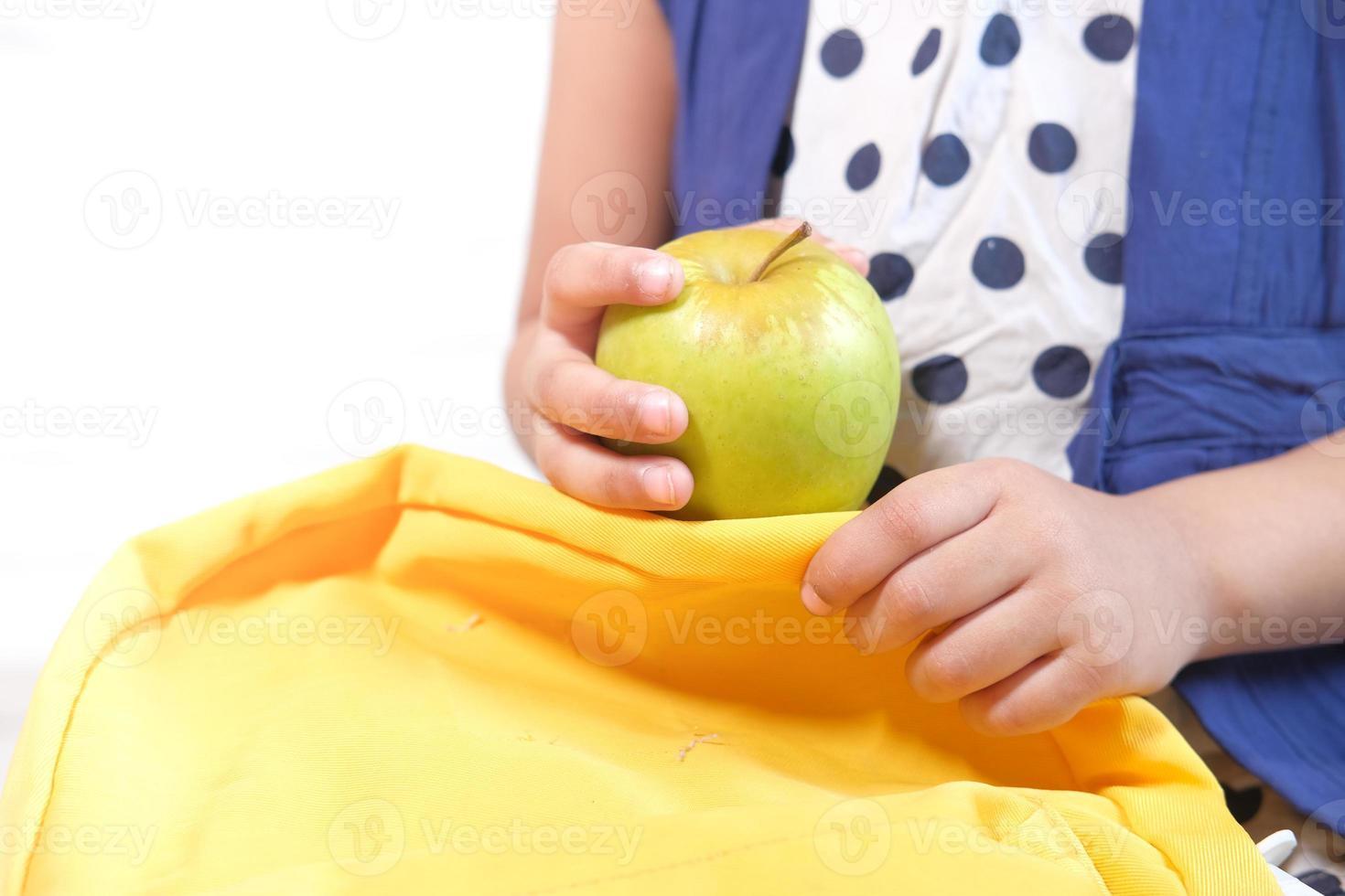 bambino che tiene mela verde su sfondo bianco foto