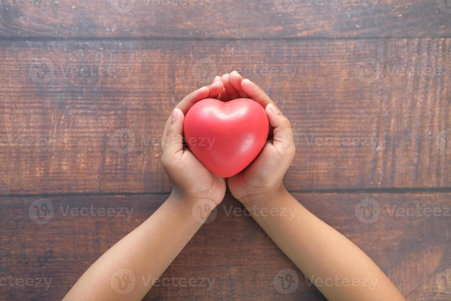 mano del bambino che tiene cuore rosso sulla tavola di legno foto