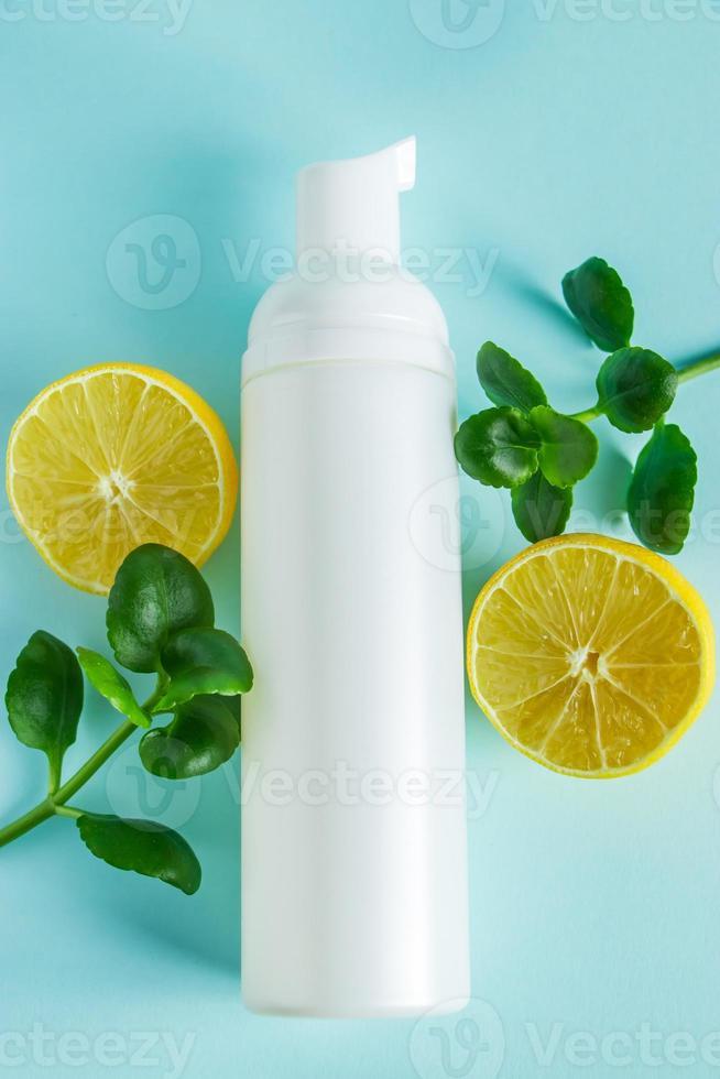 cosmetici biologici con olio di limone su sfondo blu foto