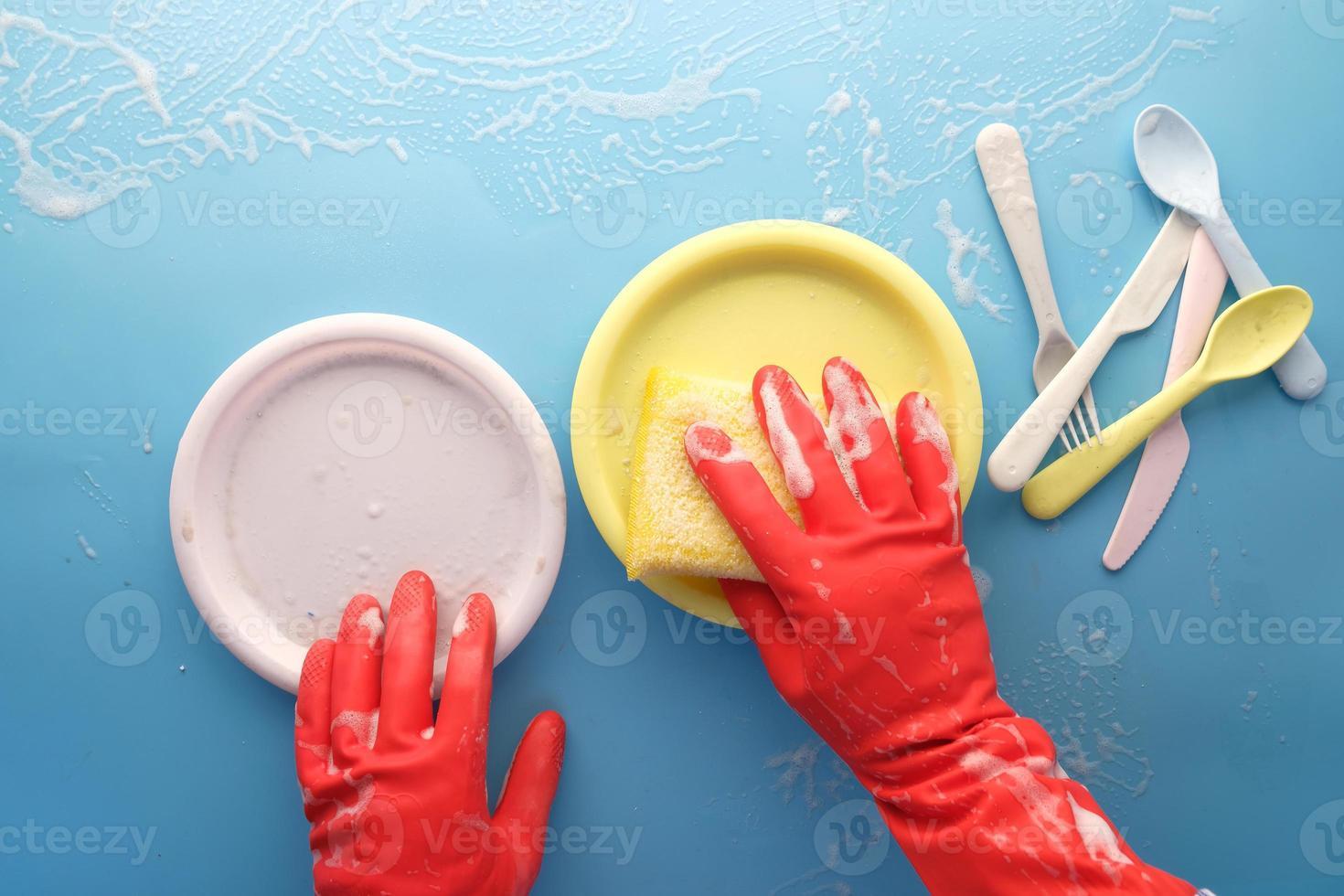 persona che pulisce piatti colorati foto