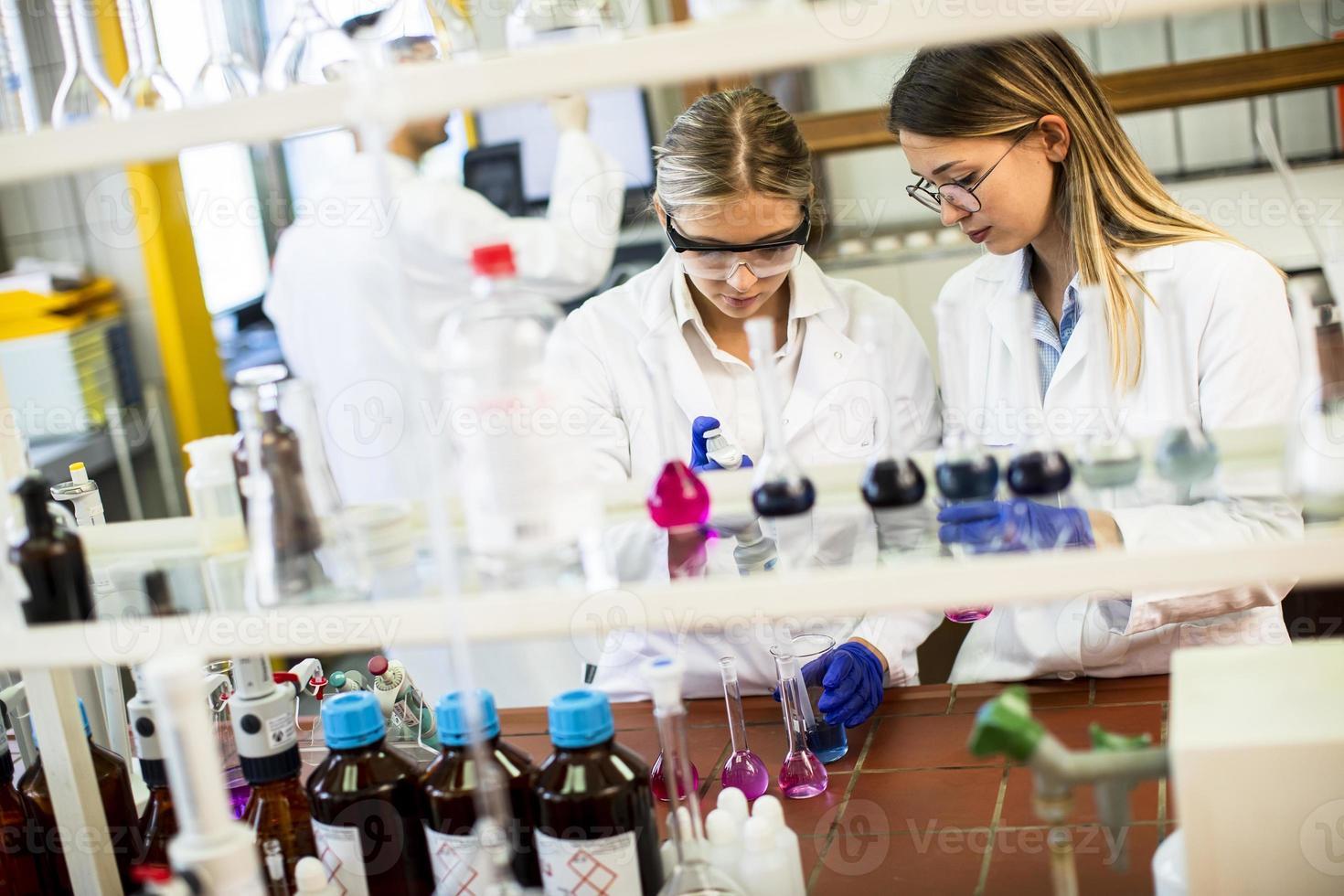ricercatrici in camice bianco che lavorano in laboratorio foto