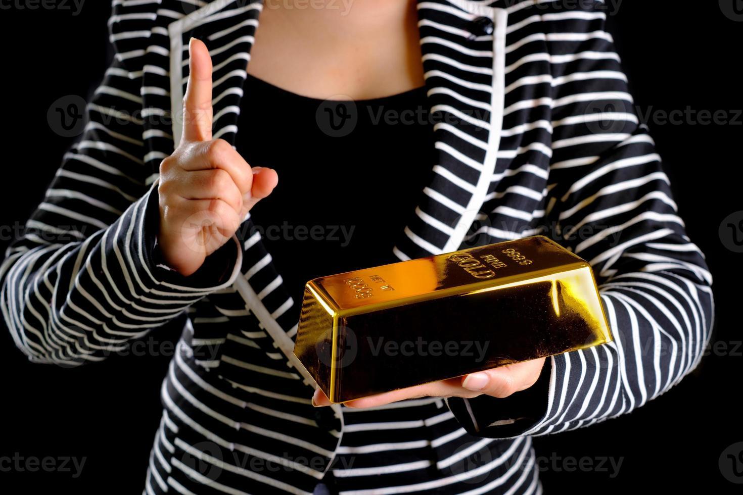 donna d'affari che tiene il lingotto d'oro foto