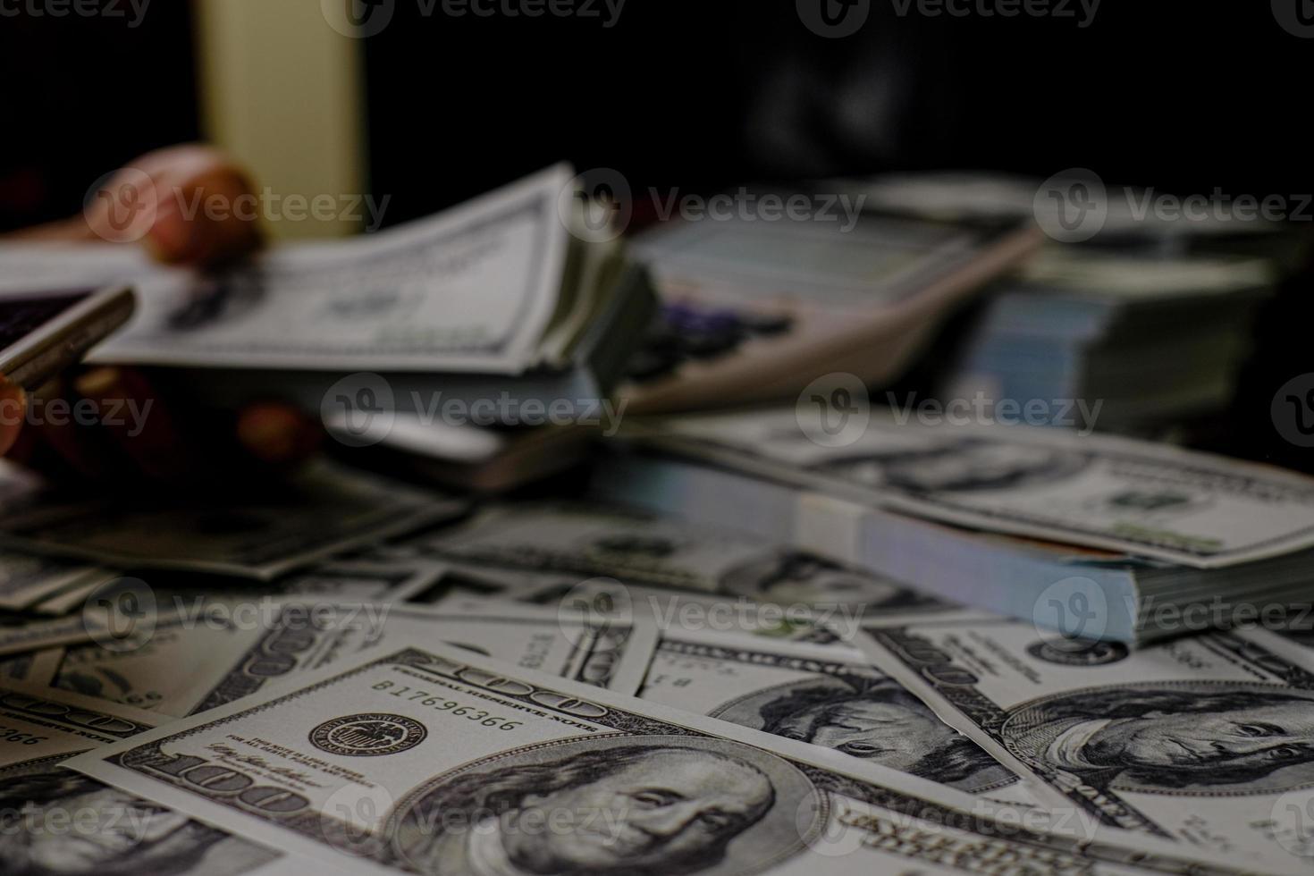mano che conta soldi su una pila di 100 banconote in dollari foto