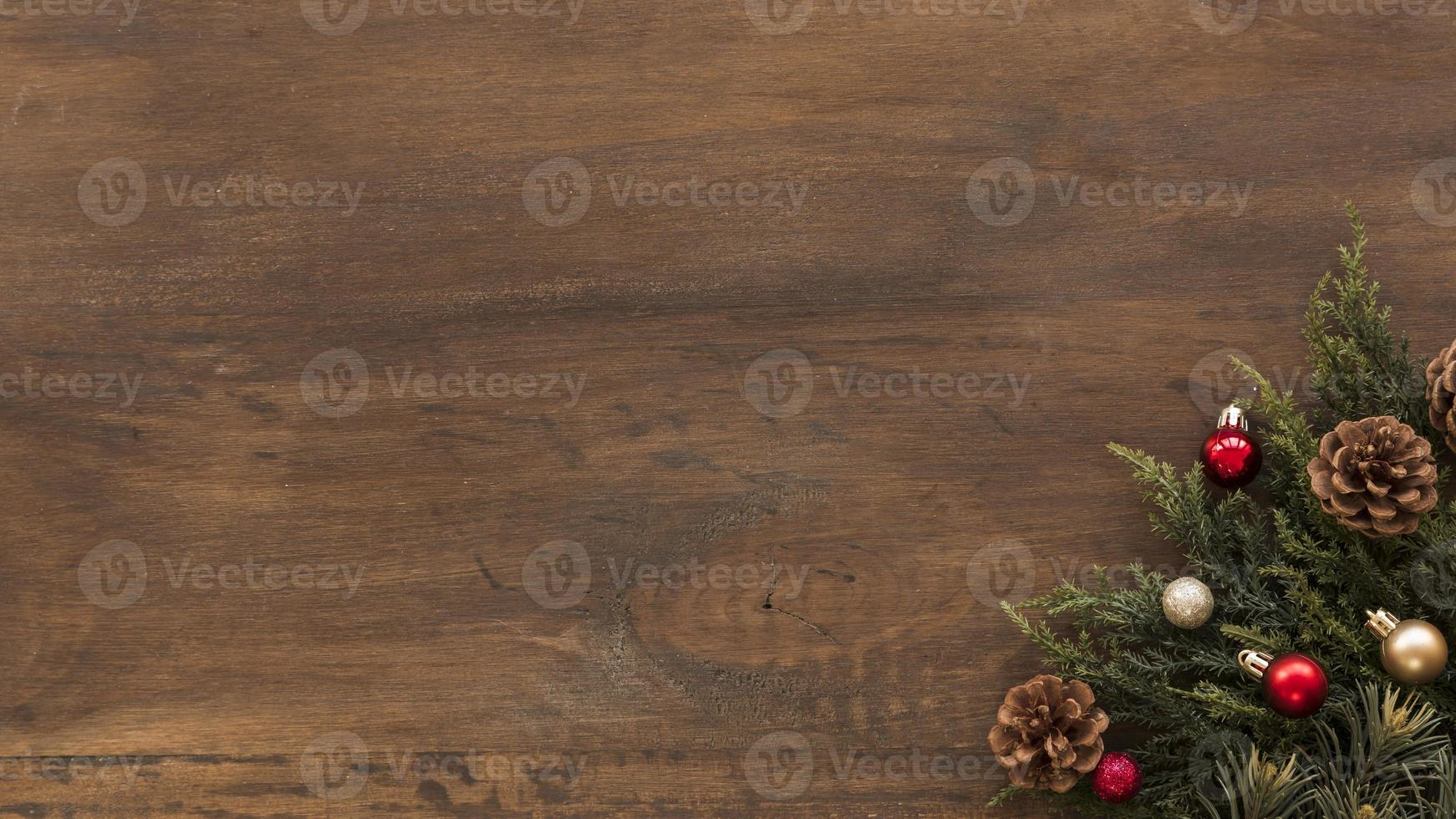 rami verdi con piccole palline lucide su fondo in legno foto