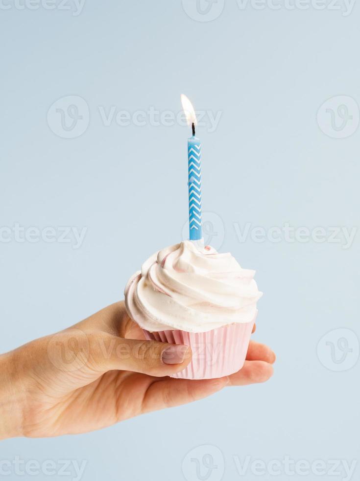 mano che tiene delizioso bigné di compleanno su sfondo azzurro foto