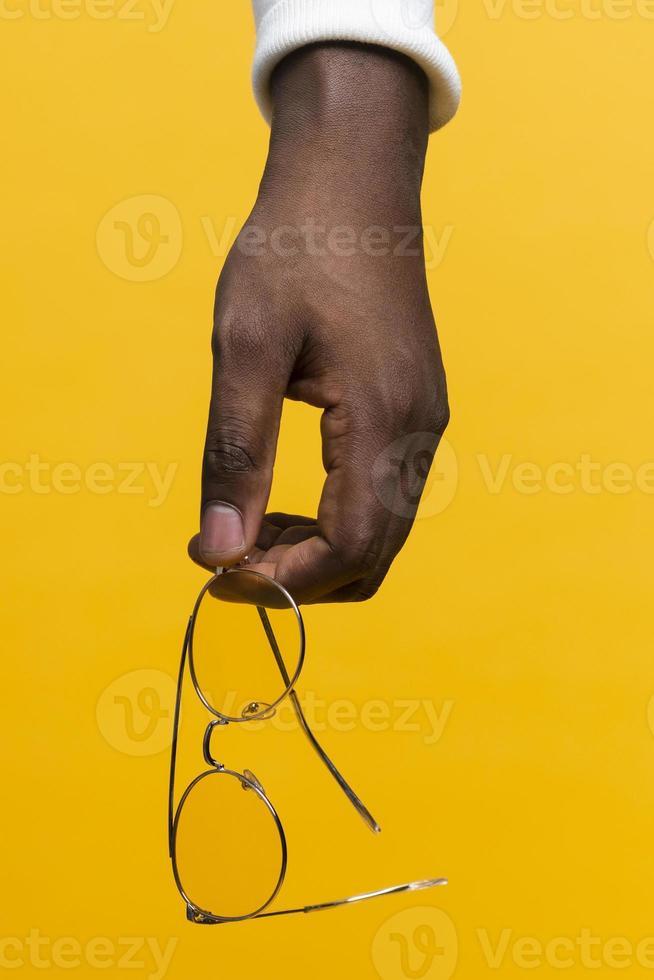 mano che tiene gli occhiali su sfondo giallo foto