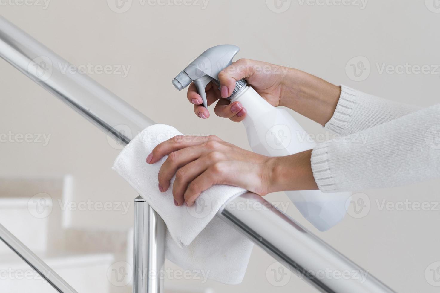 mani che disinfettano corrimano foto