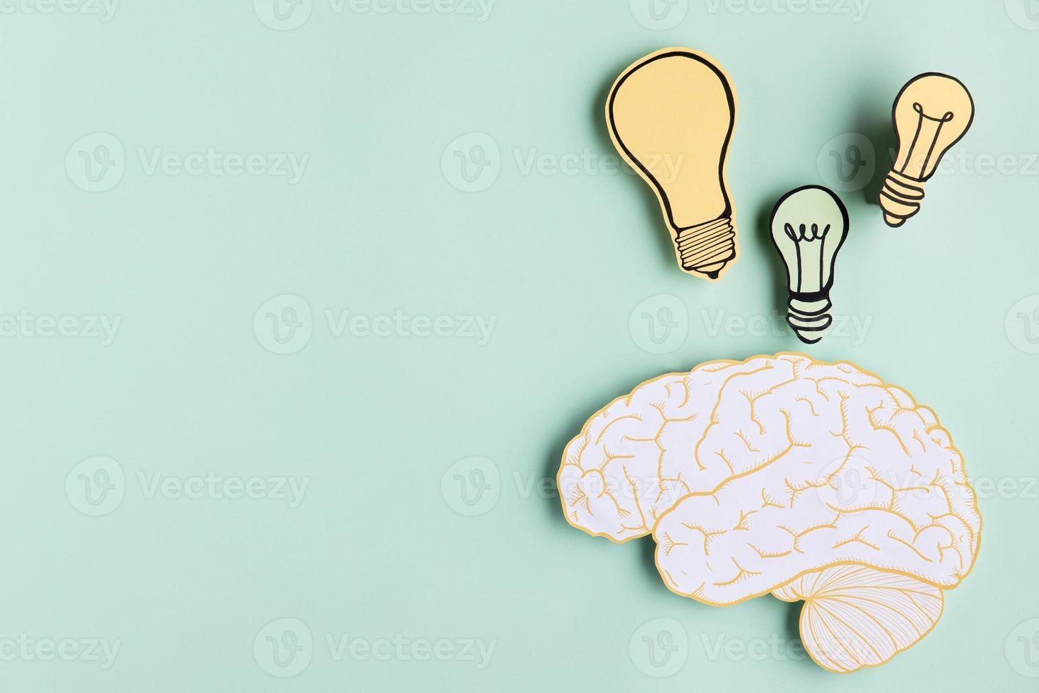copia spazio cervello di carta con lampadina su sfondo menta foto