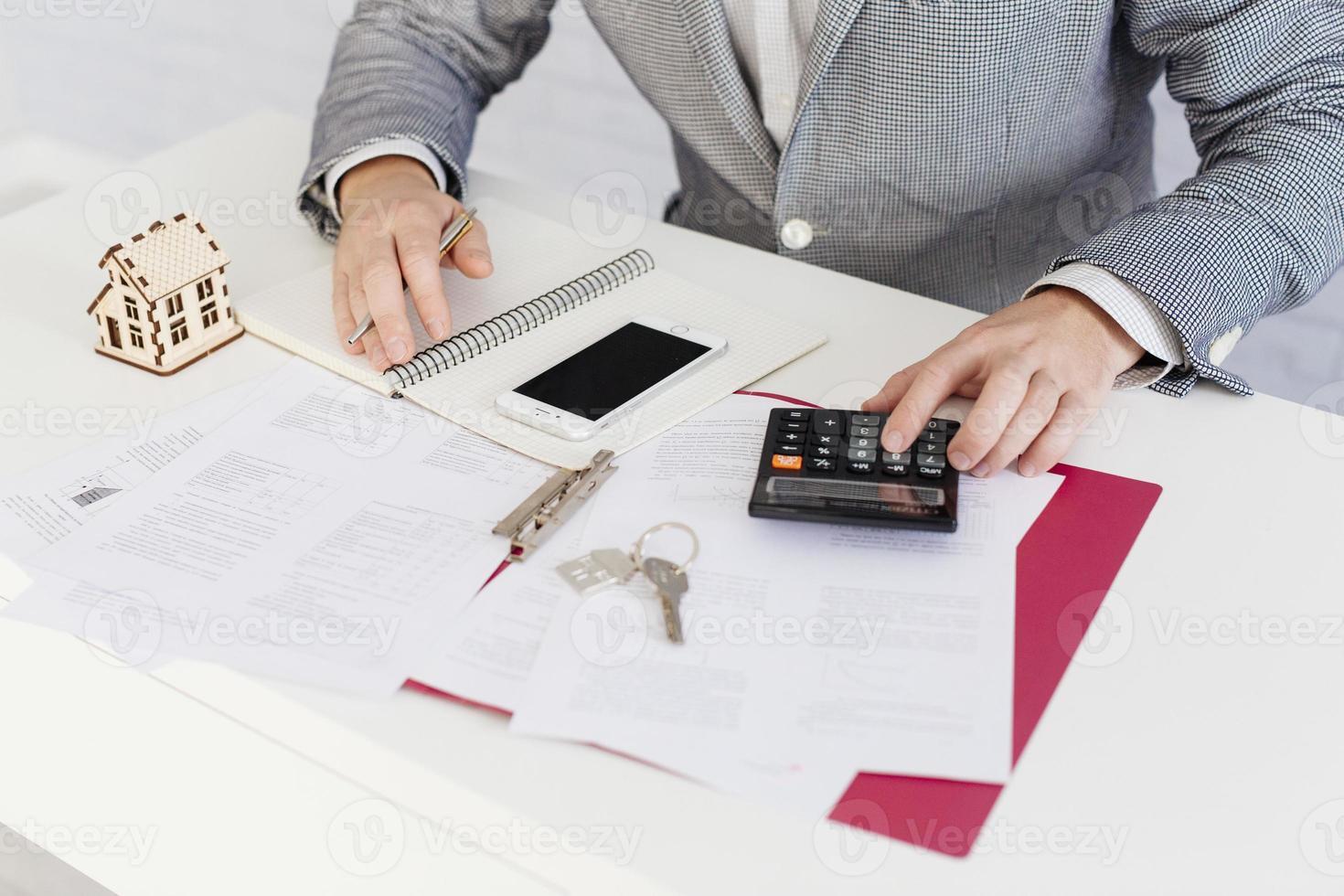 agente immobiliare ritagliata conteggio con la calcolatrice foto