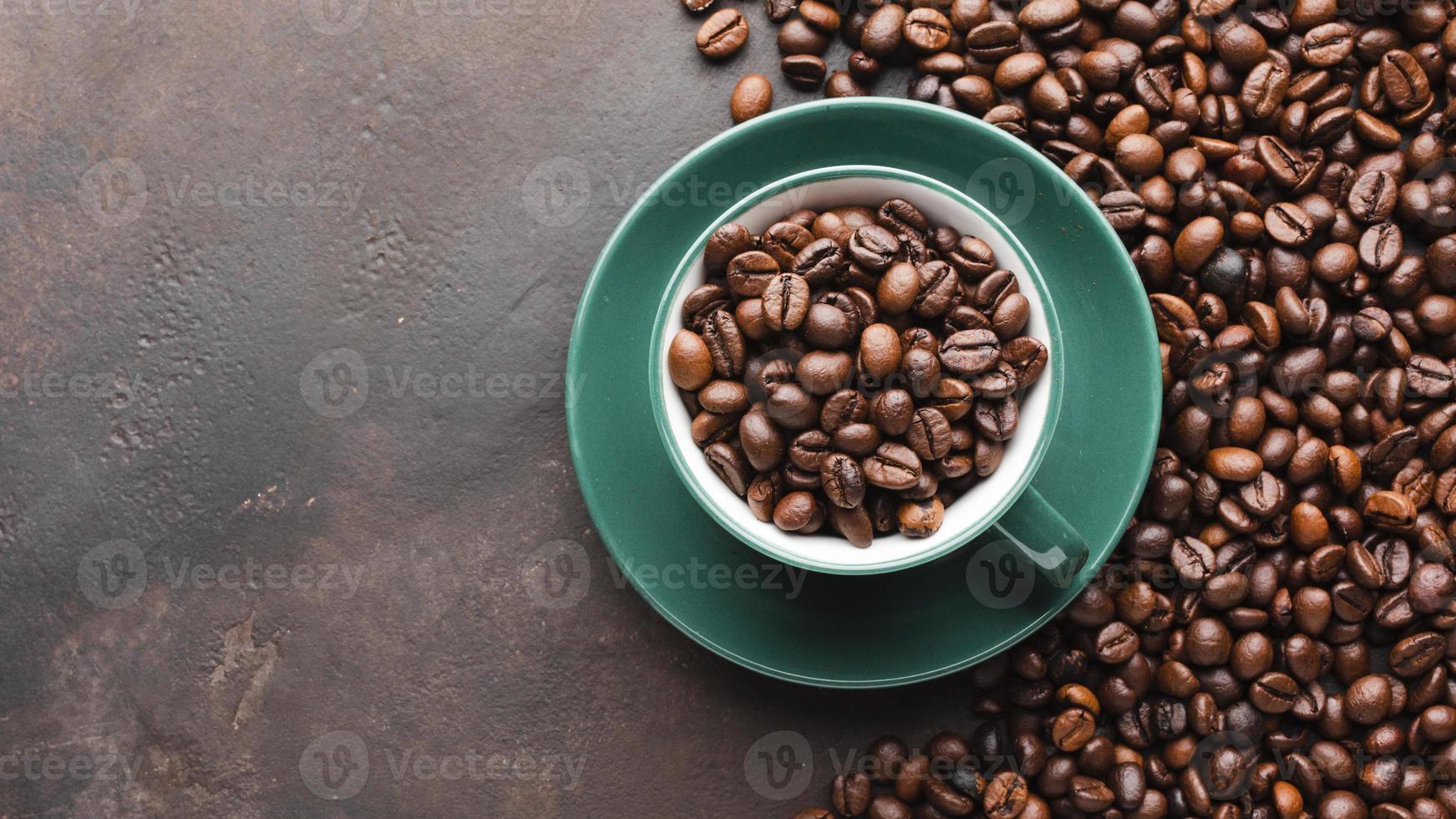 tazza piena di chicchi di caffè biologico su sfondo scuro foto