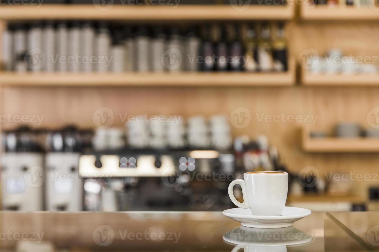 tazza di caffè espresso fresco sul bancone di vetro con sfondo sfocato foto