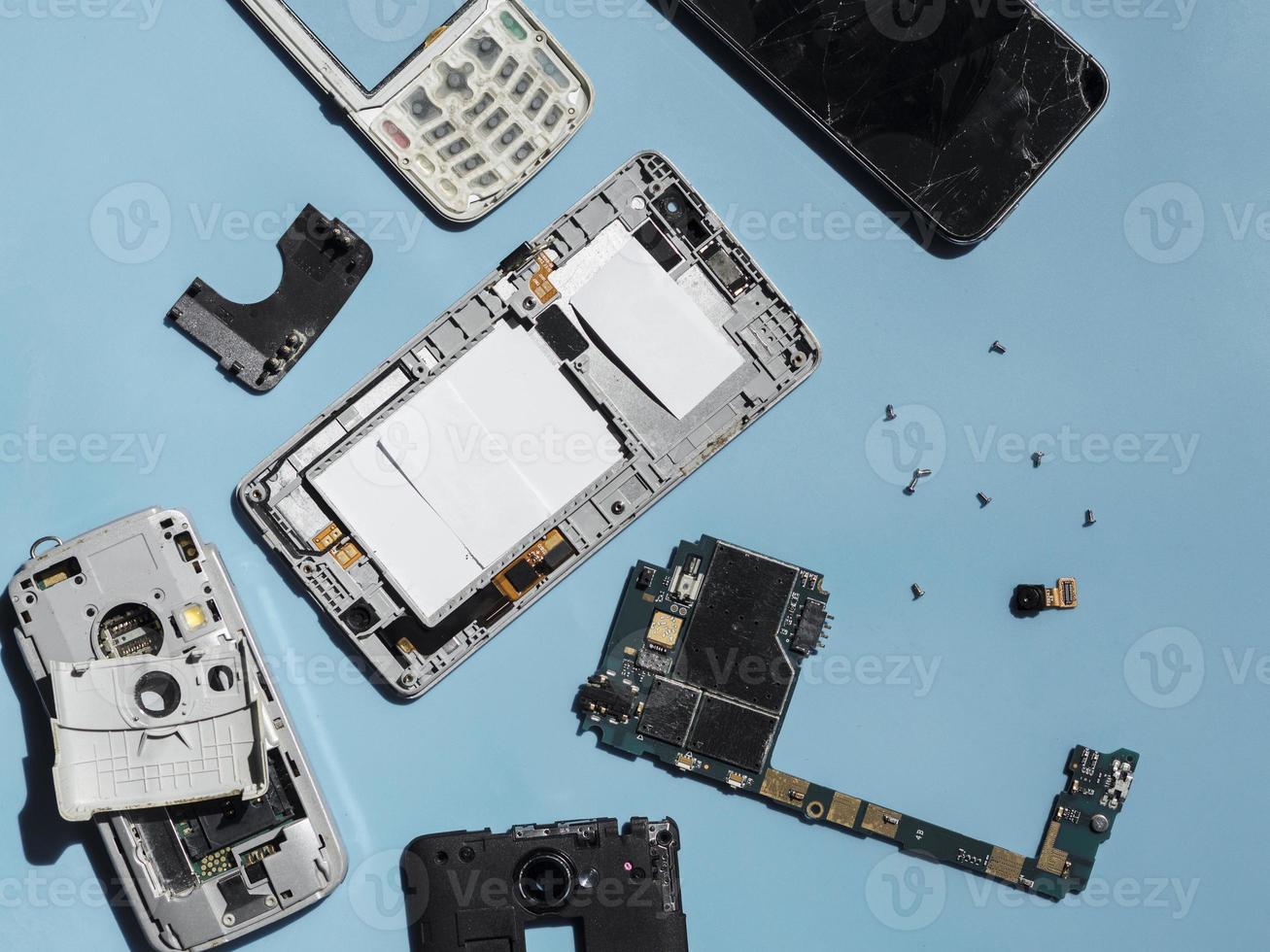 disposizione piatta di parti del telefono smontate su sfondo blu foto