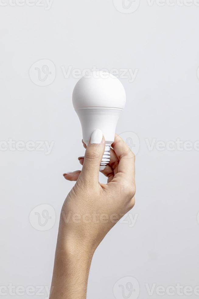 vista frontale della mano che tiene una lampadina con copia spazio foto