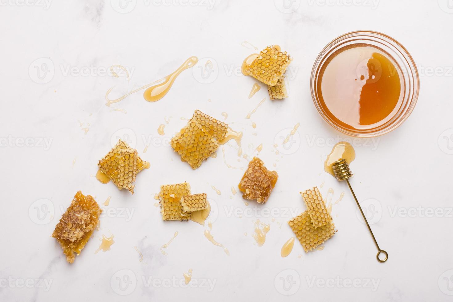 vaso di vetro pieno di miele con un cucchiaio di miele su sfondo bianco foto