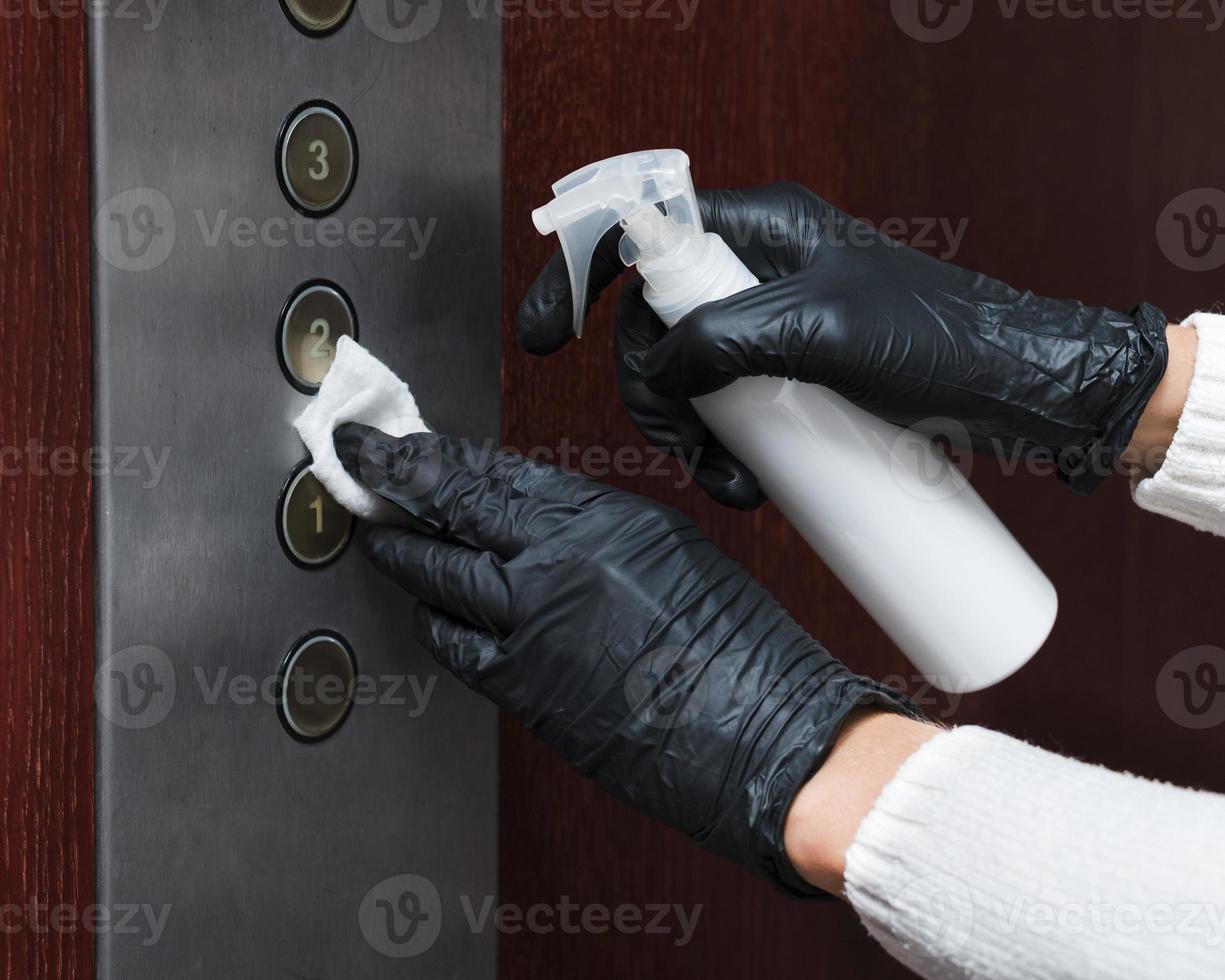 mani con guanti che disinfettano i pulsanti dell'ascensore foto