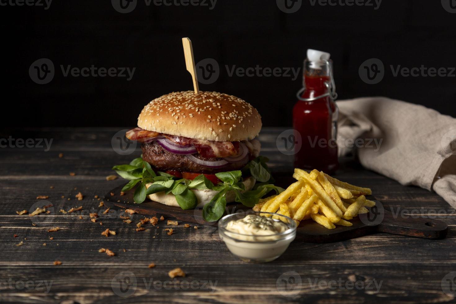 hamburger ad alto angolo con patatine fritte e salse sul tavolo foto