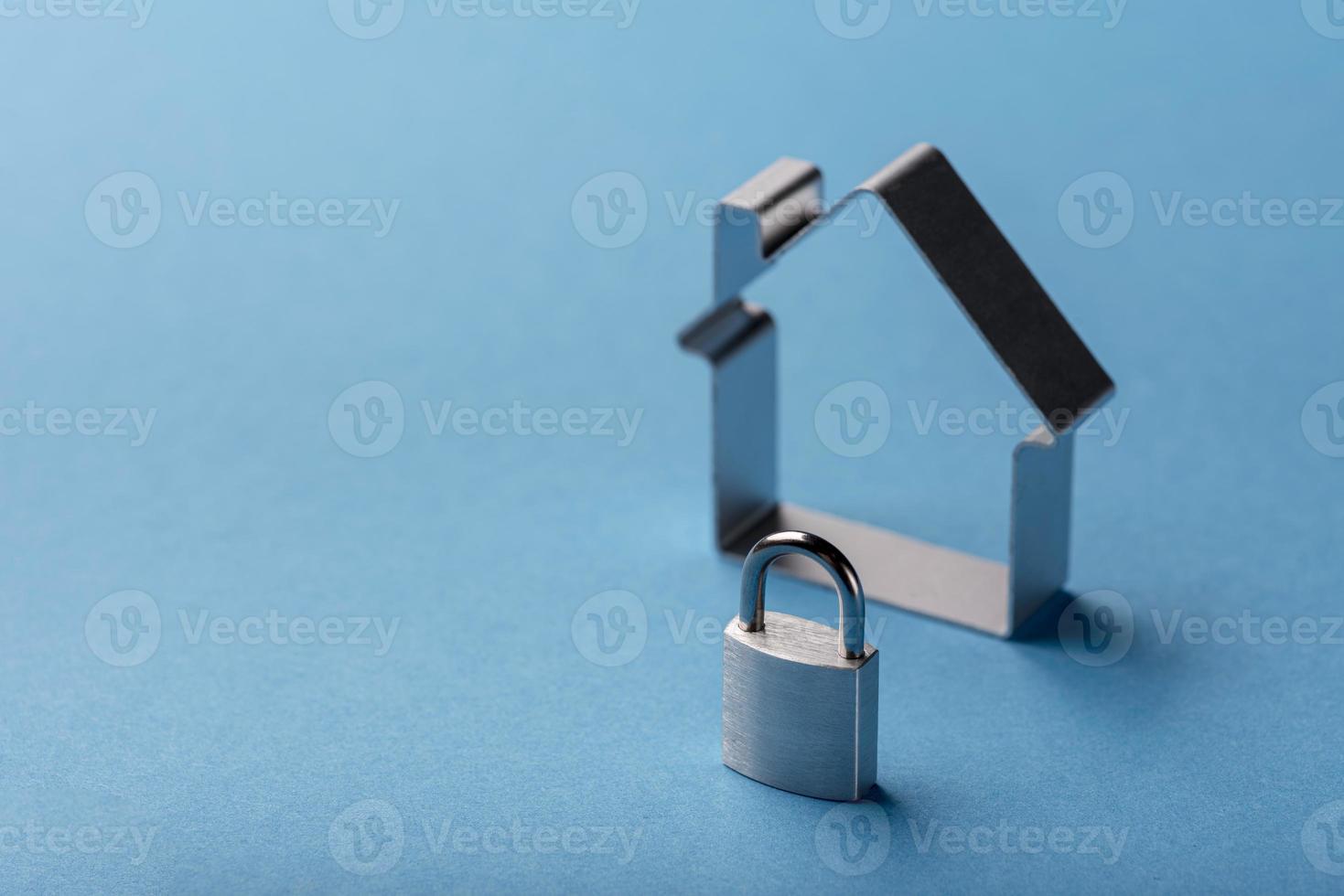 casa in miniatura ad alto angolo e serratura con spazio di copia su sfondo blu foto