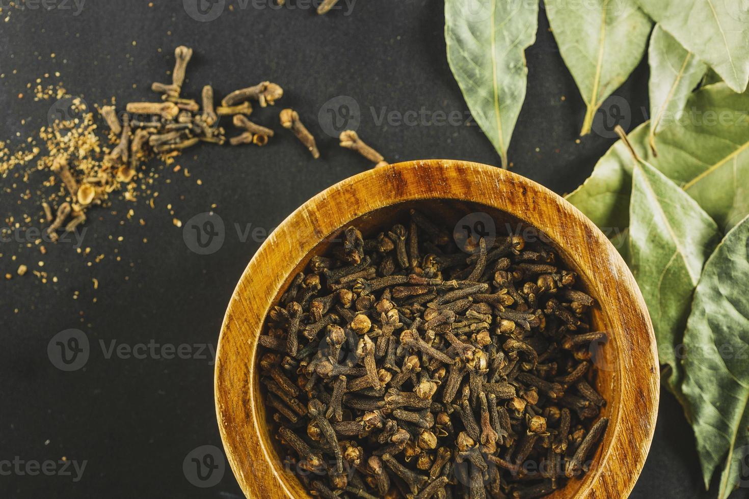 foglie di alloro vicino a ciotola con chiodi di garofano foto