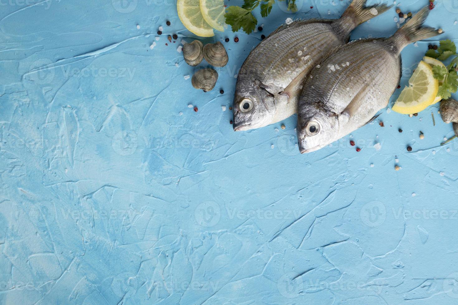 pesce piatto laici con limone e copia spazio su sfondo blu foto