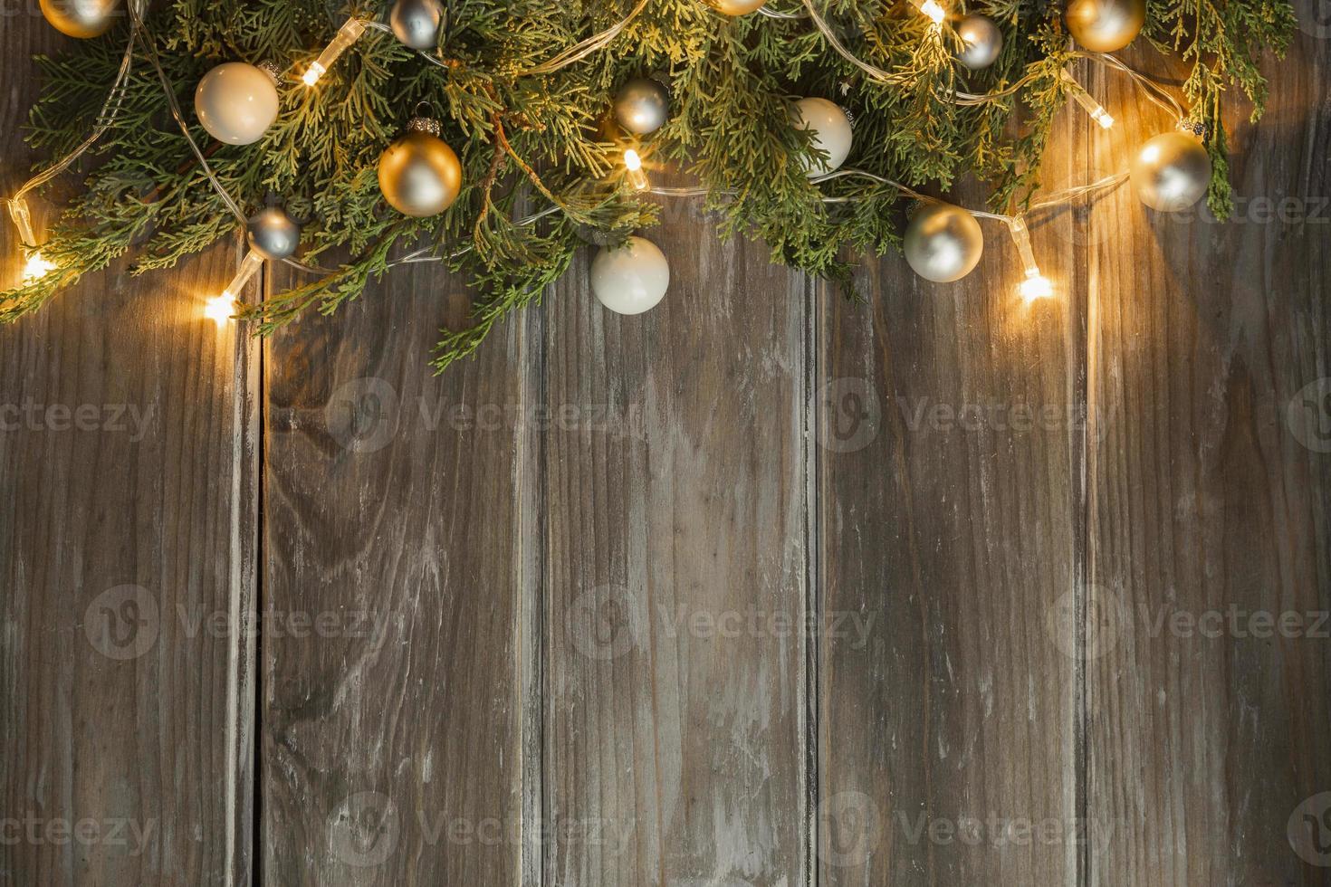 cornice piatta con albero di Natale illuminato luci su sfondo di legno foto