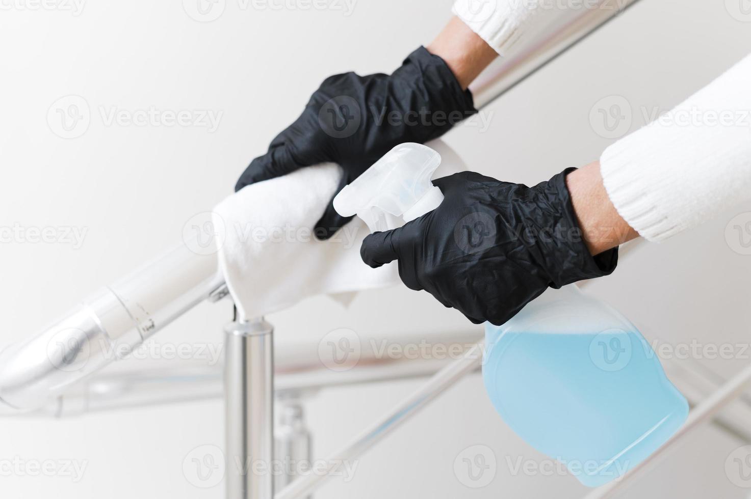 mani con guanti che disinfettano corrimano foto