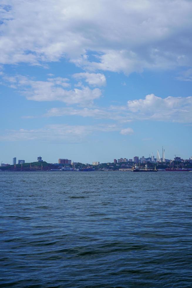 nuvoloso cielo blu su uno specchio d'acqua e una città su un litorale foto