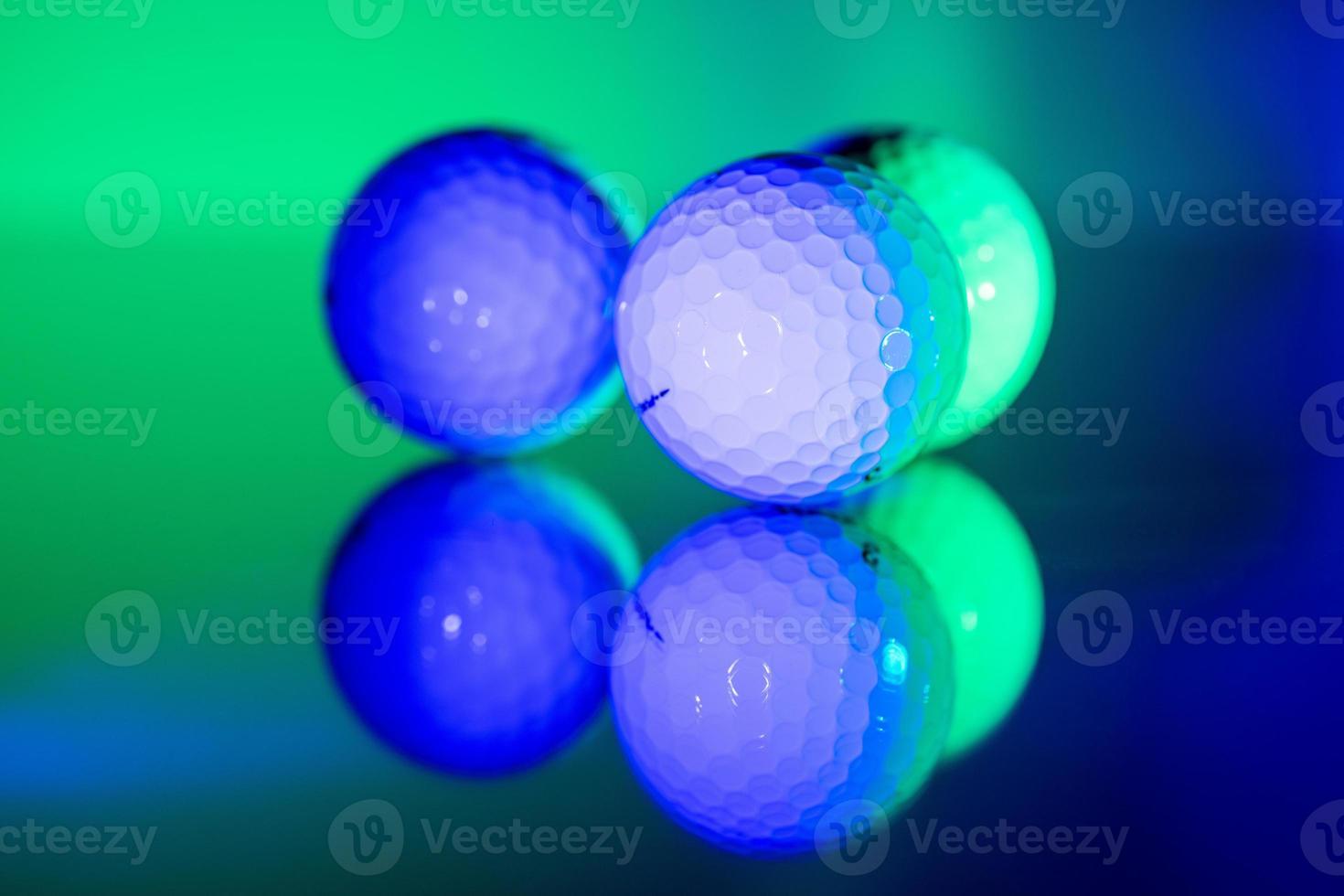 palline da golf bianche illuminate di luce verde e blu foto