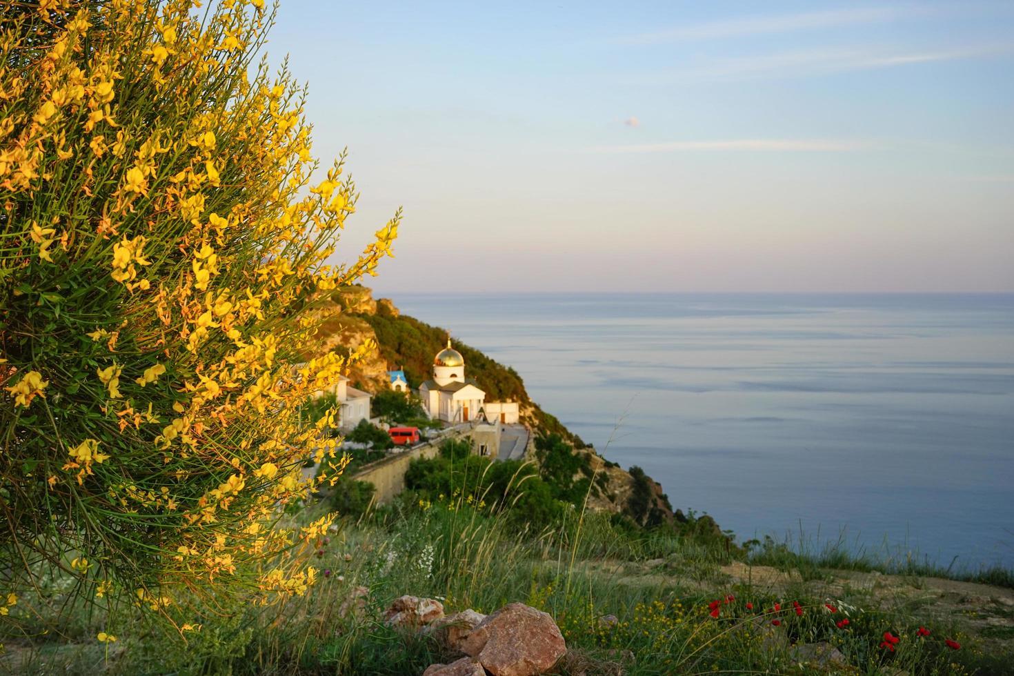 paesaggio marino con fiori, un campo erboso e una chiesa vicino a uno specchio d'acqua con un colorato cielo nuvoloso foto