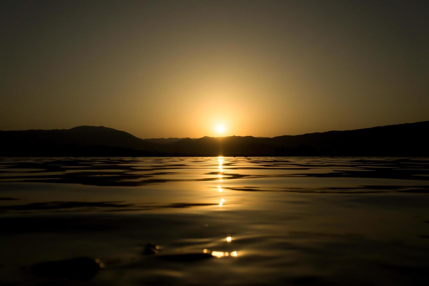vista di un lago con la luce solare riflessa sulla superficie dell'acqua foto
