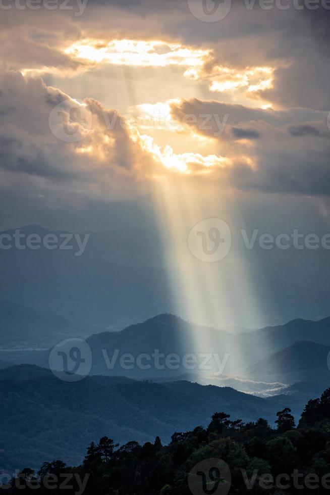la luce del sole splende attraverso il foro delle nuvole alla montagna scura foto