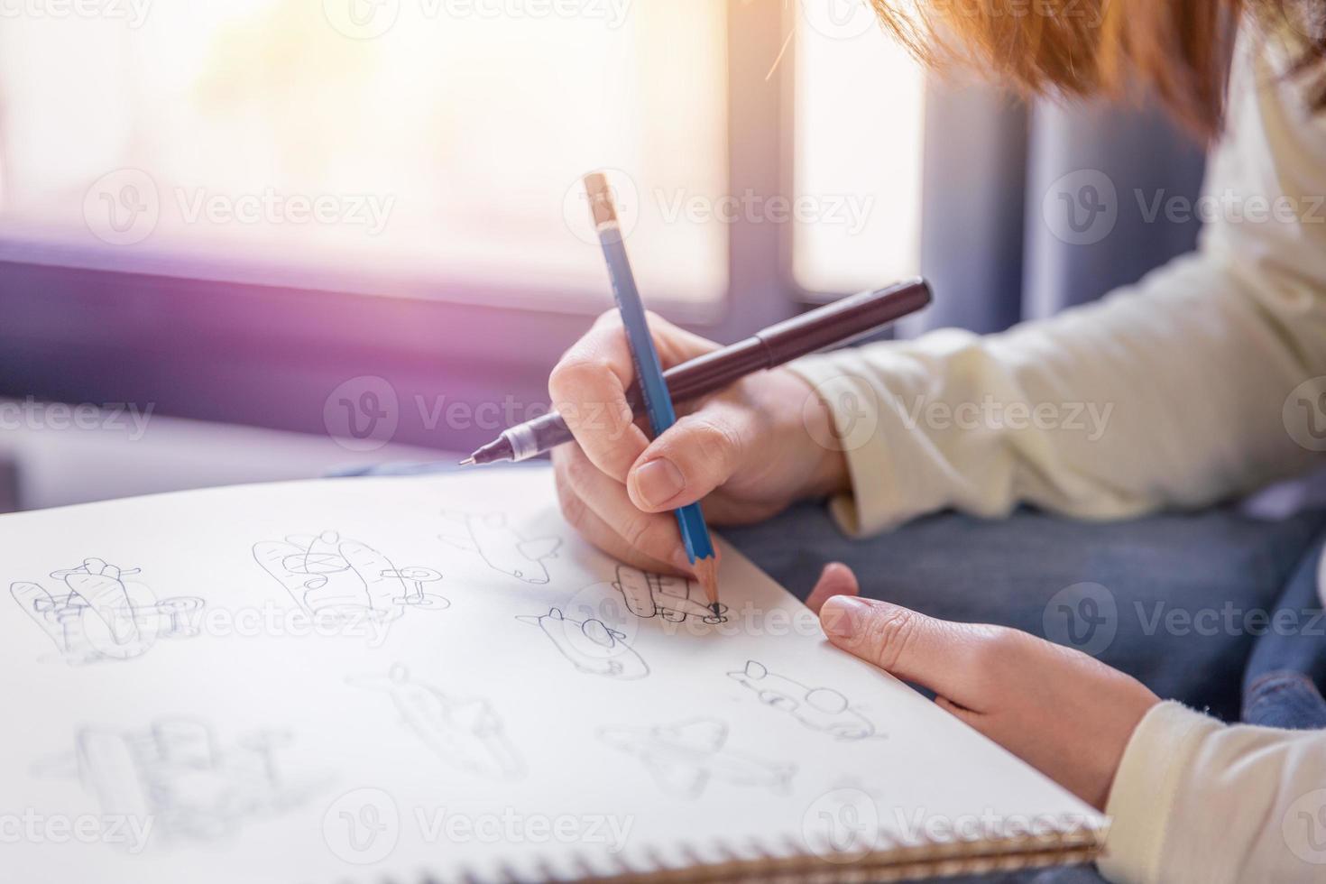la donna esegue opere d'arte disegnando a mano libera con penna e matita su carta bianca in un tono morbido di luce calda dalla finestra. foto